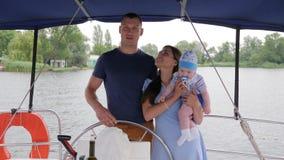 Mamã, paizinho e jovem criança durante férias de verão no rio, no esposo e na esposa com a criança pequena no iate, curso da famí vídeos de arquivo