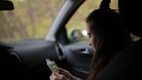 A mamã pegara a filha da escola pelo carro A filha está sentando-se no assento dianteiro é móvel e falando a minha mãe video estoque