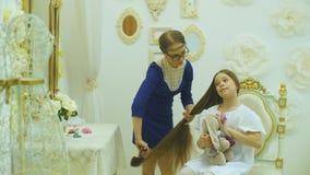 A mamã penteia seu cabelo do ` s da filha video estoque