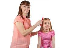 A mamã penteia seu cabelo a sua filha pequena Imagem de Stock