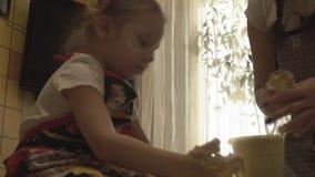 A mamã polvilha a mão de sua farinha da filha vídeos de arquivo