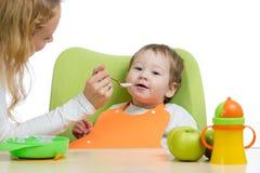 Mamã que alimenta sua criança com uma colher Mãe que dá o alimento a sua criança pequena Comida para bebê e nutrição foto de stock royalty free
