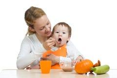 Mamã que alimenta sua criança com uma colher Mãe que dá o alimento a sua criança pequena Comida para bebê saudável e nutrição fotografia de stock royalty free