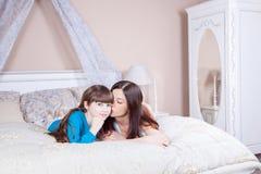 Mamã que beija sua filha bonita A mãe e a filha felizes colocam na cama que tem o divertimento, sorrindo e olhando a câmera Fotografia de Stock