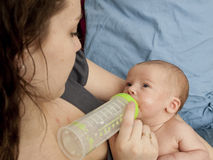 Mamã que Bottle-Feeding o bebê Foto de Stock Royalty Free