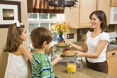 Mamã que dá a miúdos o pequeno almoço. Imagem de Stock