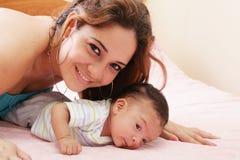 Mamã que encontra-se para baixo na cama e que guardara seu filho infantil imagens de stock royalty free
