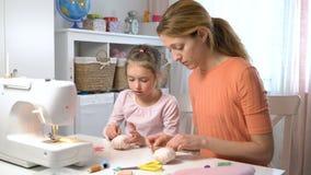 Mamã que ensina sua filha pequena costurar usando a agulha e a linha filme