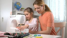 Mamã que ensina sua filha pequena costurar usando uma máquina de costura no berçário em casa video estoque
