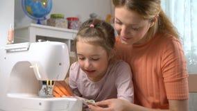 Mamã que ensina sua filha pequena costurar usando uma máquina de costura no berçário em casa filme