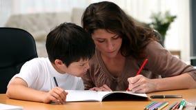 Mamã que faz trabalhos de casa com seu filho