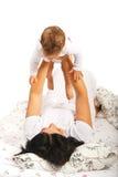 Mamã que joga com o bebê na cama Imagens de Stock Royalty Free