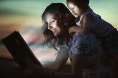 Mamã que lê livro surpreendente para sua criança Imagens de Stock