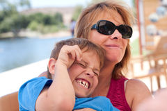 A mamã que prende o filho e o felizes ri Fotografia de Stock