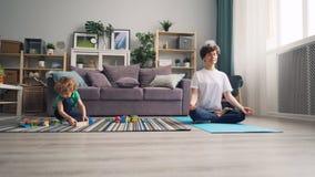 Mamã que relaxa na posição de lótus quando criança calma que joga com blocos de madeira dos brinquedos filme