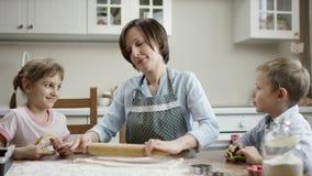 A mamã rola a lista nova de massa para cookies na tabela na cozinha com as crianças vídeos de arquivo