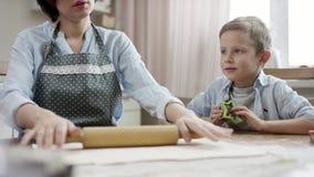 A mamã rola a massa para cookies na tabela na cozinha com o filho com foco na mamã vídeos de arquivo