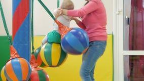 A mamã rola uma criança bonita em uma atração com um balanço de suspensão Aferrar-se do menino às cordas filme