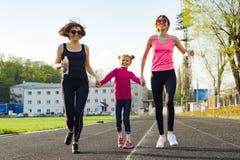 Mamã running e duas filhas imagem de stock