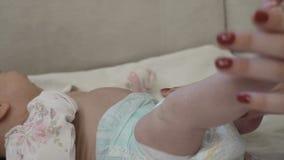 A mamã toca em sua pele do ` s do bebê video estoque