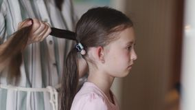 A mamã trança a menina na frente de um espelho vídeos de arquivo