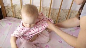 A mamã veste o bebê pequeno filme