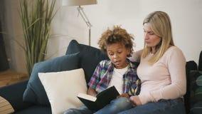 Mamãe e filho da mulher que sentam-se no sofá do conforto e no livro de leitura filme