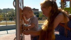 Mamãe que joga com o bebê no parque vídeos de arquivo
