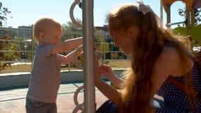 Mamãe que joga com o bebê no parque filme