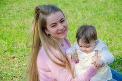 Mam? com o beb? na roupa brilhante em uma manta cor-de-rosa no direito verde Fam?lia que descansa no parque em um dia morno imagem de stock royalty free