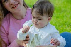 Mam? com o beb? na roupa brilhante em uma manta cor-de-rosa no direito verde Fam?lia que descansa no parque em um dia morno foto de stock