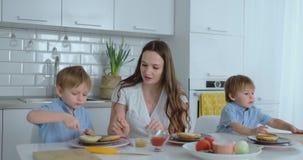 Mam? con dos ni?os en la cocina en la tabla que prepara la hamburguesa para el almuerzo almacen de metraje de vídeo