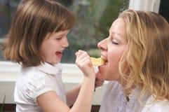 Mamã de alimentação da filha um Apple Imagem de Stock