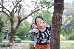 Mam? de sorriso que leva sua menina da crian?a pequena no jardim com inteiramente a flor do rosa da queda ao redor Fam?lia loving imagem de stock
