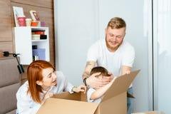 Mam? del pap? y peque?o juego del hijo en el dormitorio con las cajas de papel imágenes de archivo libres de regalías