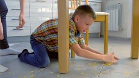 A mam? discute seu filho para o alimento dispersado no assoalho da cozinha e f?-lo limpar Flocos de milho limpos do menino acima  video estoque