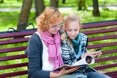A mam? e a filha leram um compartimento no parque fotografia de stock