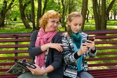 A mam? e a filha leram um compartimento no parque foto de stock royalty free