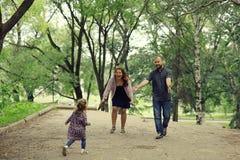 A mamã e a filha nova e o paizinho que andam no verão estacionam Fotografia de Stock Royalty Free
