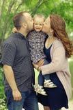 A mamã e a filha nova e o paizinho que andam no verão estacionam Imagem de Stock