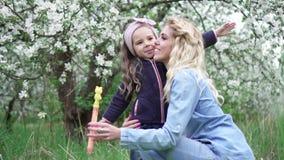 Mam? e filha pequena que jogam com bolhas de sab?o no jardim de floresc?ncia, movimento lento filme