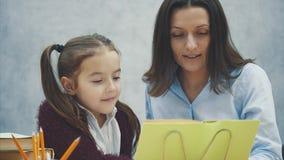 A mam? e a filha sentam-se na tabela e leem-se um livro Durante este fundo cinzento vídeos de arquivo
