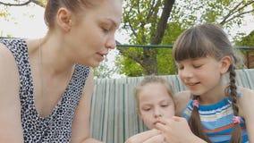 Mam? e filhas que sentam-se em um balan?o do jardim, em rela??es de fam?lia dos pais e em crian?as filme