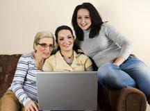 Mamã e filhas que têm o divertimento com portátil Fotografia de Stock