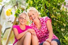 Mamá e hija que se sientan en el jardín que disfruta de la sol Foto de archivo libre de regalías