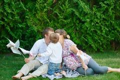 Mamá e hijo del papá que se sientan en una manta en el parque y el beso Imagen de archivo