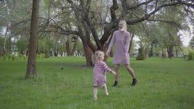 Mam? e hijo, hija que juega en el parque Dos madres lindas que juegan con ellos a niños en parque asombroso verde en la naturalez metrajes
