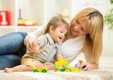 Mamá e hijo que juegan los juguetes del bloque en casa Imagenes de archivo