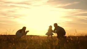 A mam? e o paizinho que jogam com a crian?a no parque no por do sol, crian?a tomam as primeiras etapas família feliz que joga com video estoque