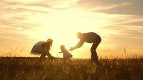 A mam? e o paizinho que jogam com a crian?a no parque no por do sol, crian?a tomam as primeiras etapas filha pequena feliz que jo filme